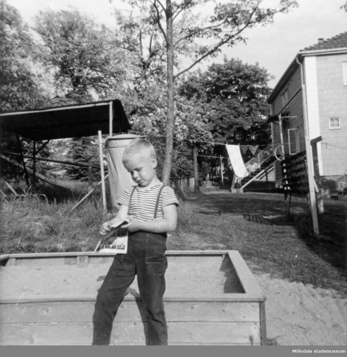 En pojke tittar i en serietidning, ståendes brevid en sandlåda. I bakgrunden hänger tvätt på Brunnsgatan 7, 1965.