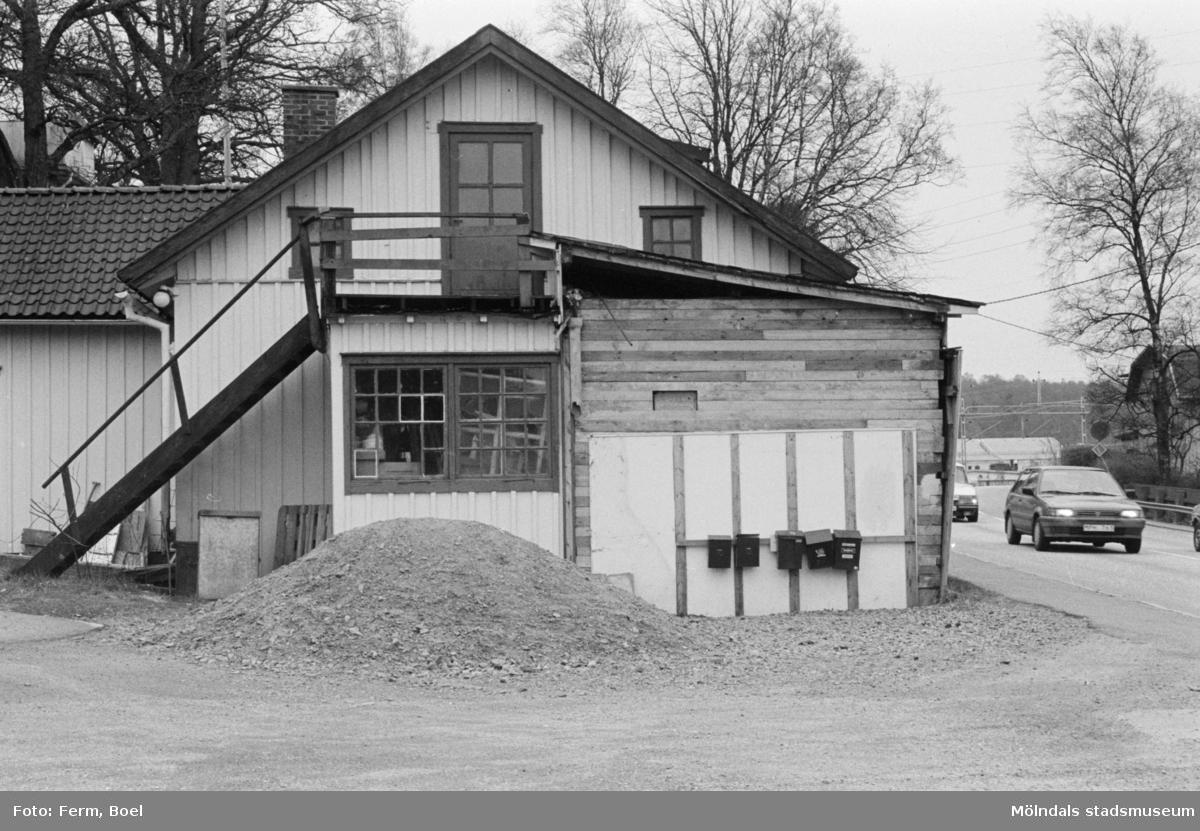 Vid Gamla Riksvägen i Kållereds centrum byggde John Lindström ett snickeri och drev det från 1930 till 1970-talet. I många år stod snickeriet som det lämnades - fyllt av maskiner, mallar, fanér- och färgprover. Senare blev det hantverksgården Ekebacken. Fotografiet togs från norr, 1992.