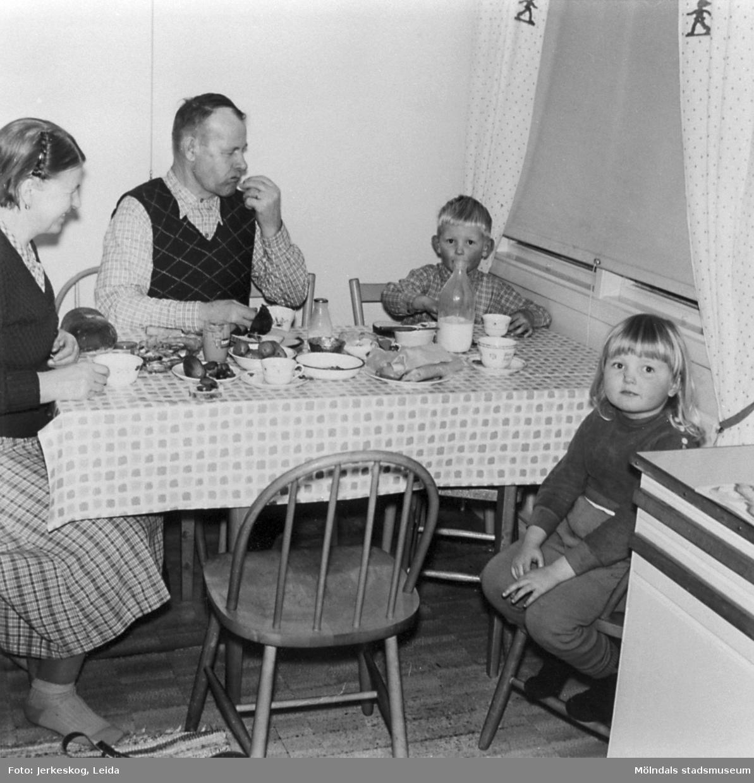 Trofina och Fedosja Jeutitonen äter kvällsmål i köket tillsammans med barnen Ulf och Marita Jerkeskog på Idunagatan 39, 1957.