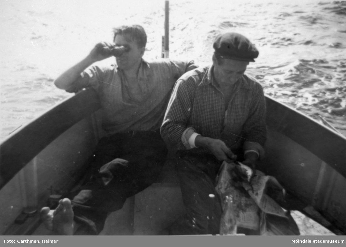 Helmer Garthmans arbetskompisar är ute med båt och fiskar. En man tittar i kikare utöver vattnet och den andre rensar fisk på ett tidningspapper. Näset, 1950-tal. Skänkt av sonen Alf Garthman som arbetade under många år på Mölndals stadsmuseum.