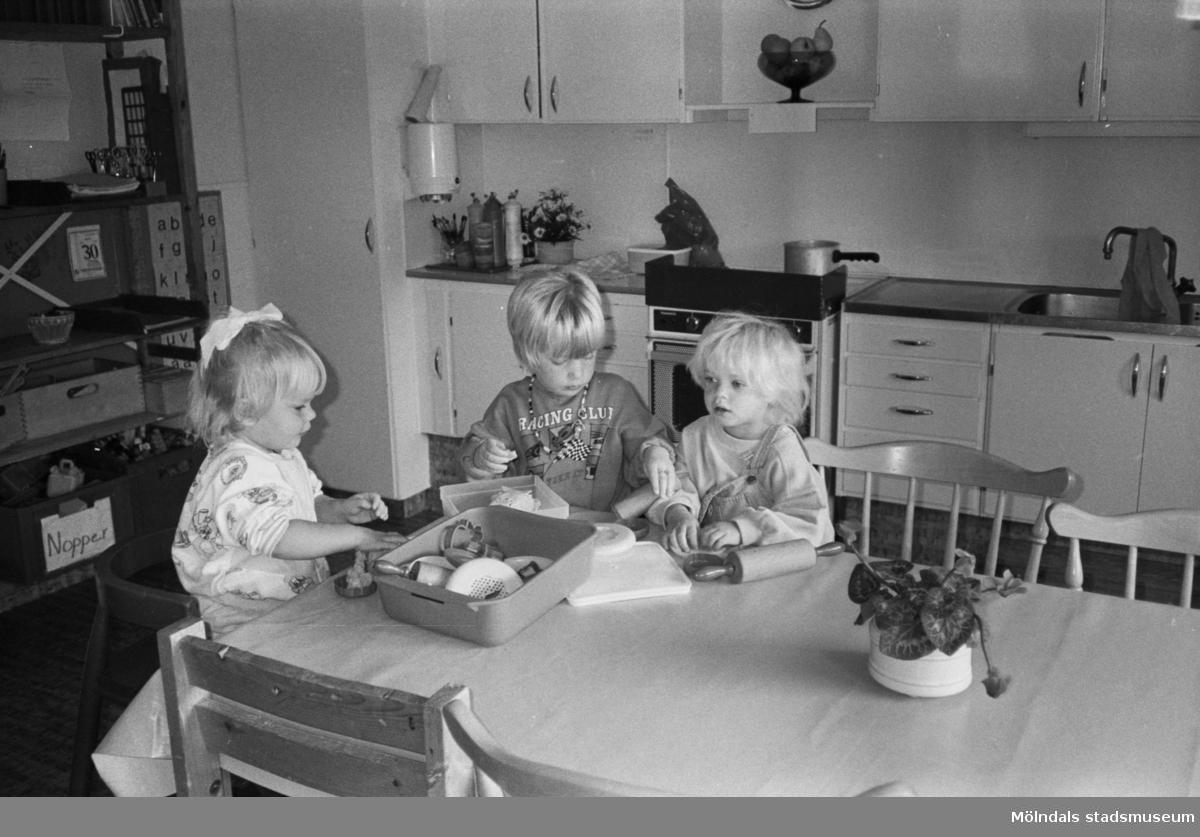 """Tre små barn sitter vid köksbordet på Katrinebergs daghem. De """"bakar kakor"""" med hjälp av leksaker och modellera. I bakgrunden ser man en bokhylla samt köksskåp."""