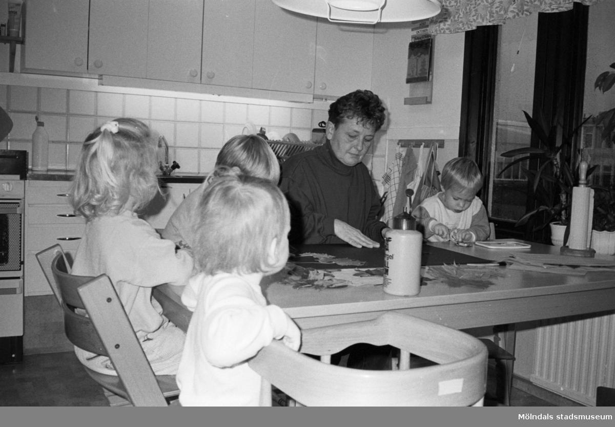En kvinna och tre barn sitter runt ett bord. Ett utav barnen sitter på en trip trap stol och ett barn står bredvid en barnstol. De lägger pussel och pysslar, i köket på Katrinebergs daghem.
