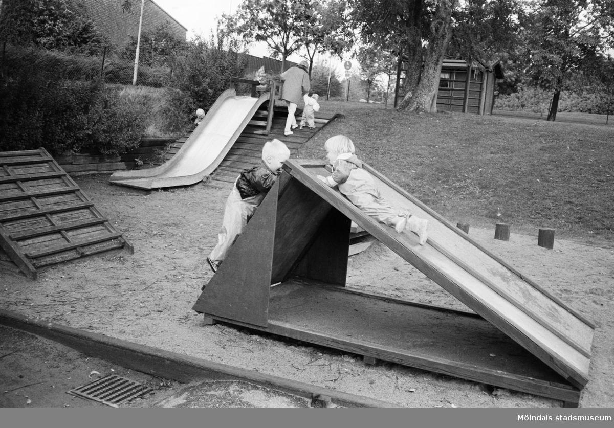 Lekplatsen vid Katrinebergs daghem, 1992. Man ser ett lågt hus att klättra på samt två rutschkanor. Den ena löper utför en backe och den andra som står i en sandlåda.