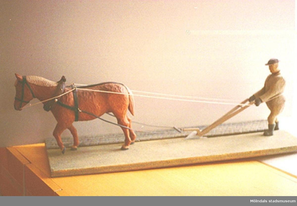 """En förspänd arbetshäst drar en fåra i jorden. En man går bakom och håller i de långa tömmarna till plogen som plöjer åkern. Harry Bergmans """"gubbar"""" (träfigurer). Liknande foto som 1994_0962."""