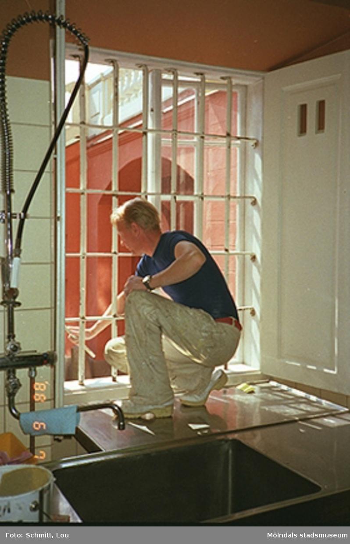 En man som målar ett fönster inomhus på Gunnebo slott.