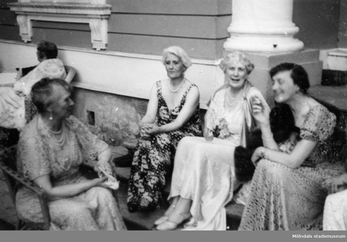Tre kvinnor sitter på en trappa och en kvinna sitter i en stol mittemot dem. Gunnebo slott, 1937.
