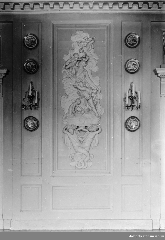 Reliefdekor på matsalens norra vägg. På varje sida hänger en lampett med plats för tre ljus samt porslinsfat. Gunnebo slott, 1930-tal.