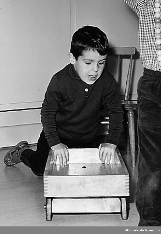 En pojke skjuter en liten trävagn framför sig vid Holtermanska daghemmet 1953.