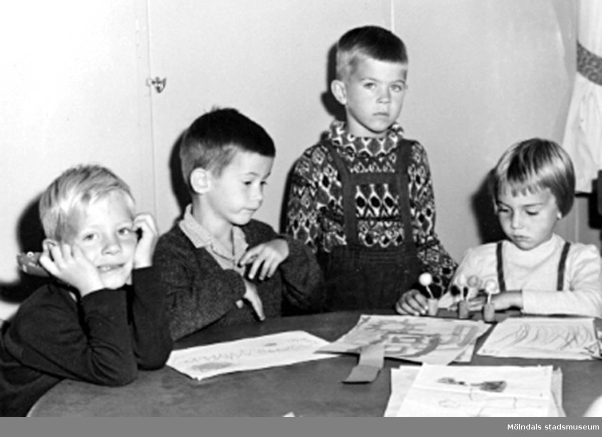 Fyra barn som sitter vid ett bord där det ligger målade teckningar. Holtermanska daghemmet 1953.
