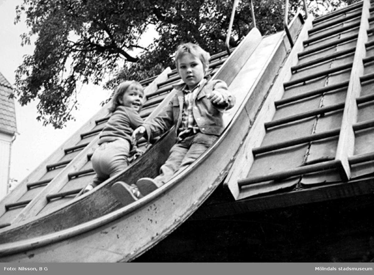 Två barn i en rutschbana. Holtermanska daghemmet juni 1974.