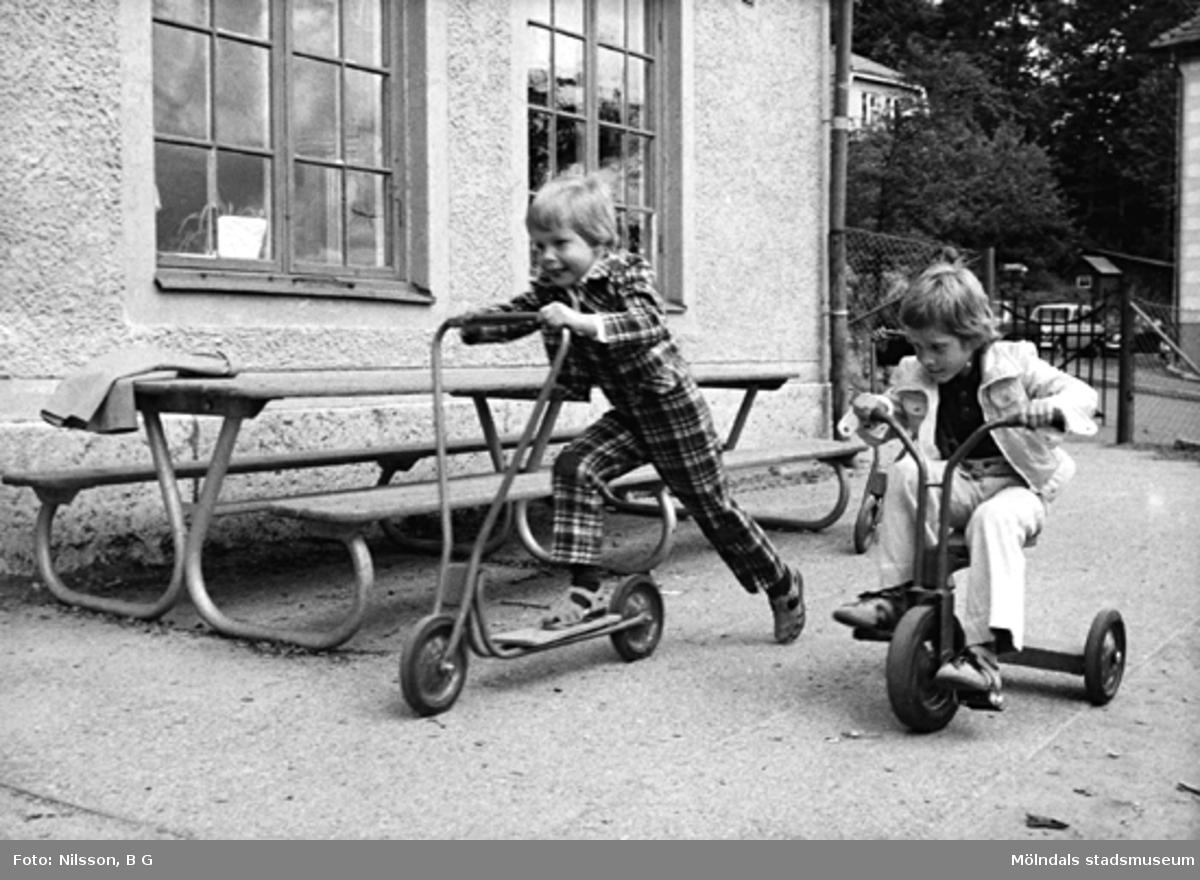 Två pojkar som cyklar på en trehjuling och en sparkcykel. Holtermanska daghemmet juni 1974.