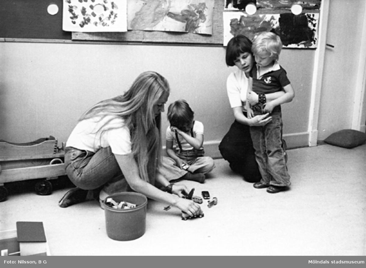 Två barn och två fröknar leker med bilar på golvet. Holtermanska daghemmet maj 1975.