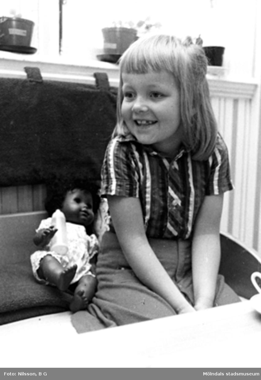 En flicka med en docka bredvid sig. Holtermanska daghemmet, okänt årtal.