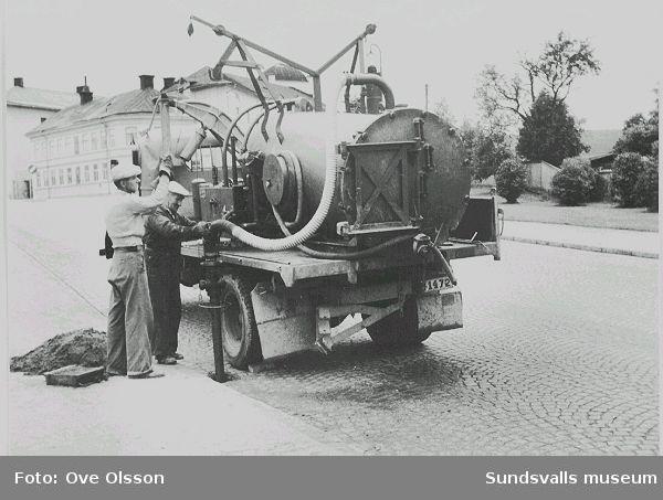 """Text: """"Här är renhållningsverkets mannar sysselsatta med brunnsrensning. Efter ett skyfall som här är fråga om, ha de bråda dagar. Väst på sta´n, f.d. Grönborgs bryggeri i bakgrunden, utfartsväg mot Östersund""""."""
