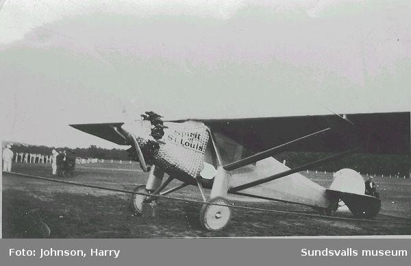 """Text på baksidan: """"Lindbergs flugskep Wi tog detta här kort i sommar. Harry Johnson"""". Charles Lindbergh (1902 - 1974) genomförde 1927 den första ensamflygningen över Atlanten med sitt plan """"Spirit of St. Louis""""."""