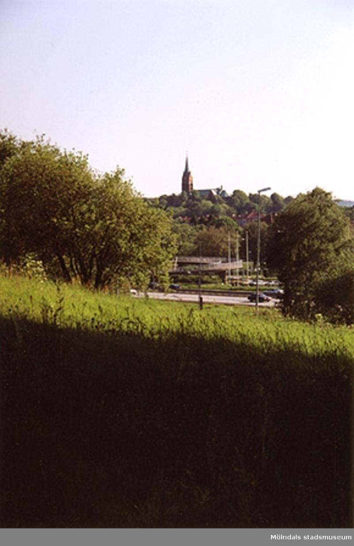 Utsikt över ängen mot Fässberg kyrka i bakgrunden. Järnvägsgatan i bildens mitt.
