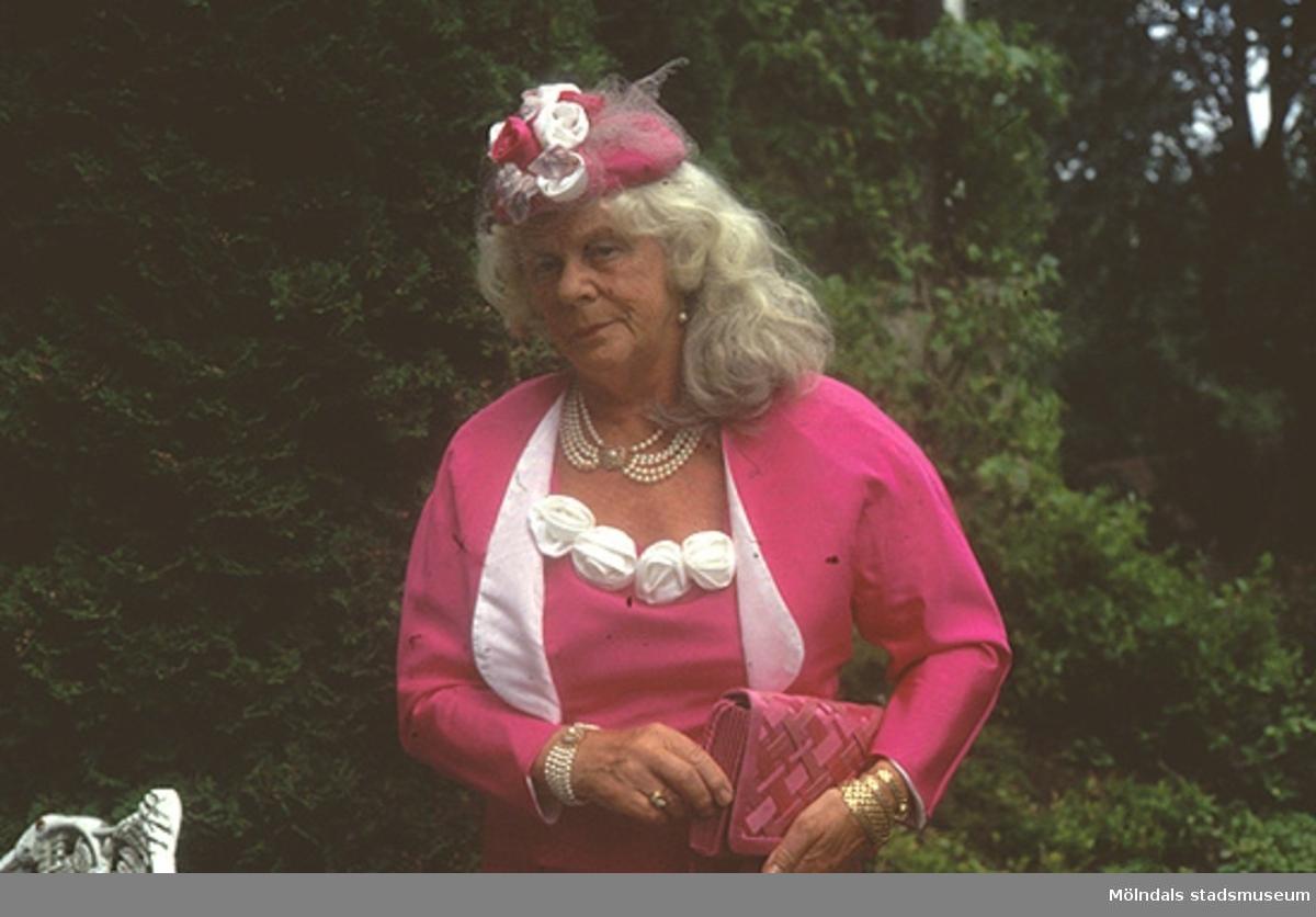 Margit Wannerberg står i en trädgård, iförd sin 1990-tals dress. Plaggen finns på museet: klänning/jacka/sjal (inv.nr: 03335_1-3), handväska (invnr: 03336) och hatt (inv.nr: 03339).