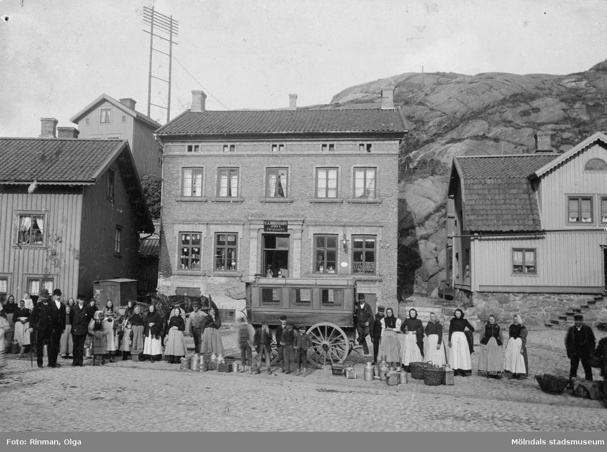 Gamla torget på 1880- eller 90-talet. Mitt på torget står hästomnibussen Mölndal med ägaren Johan Svensson till höger.På baksidan av fotot står skrivet: Data finns i fotograf Kjellmans samlingar.Bilden något beskuren från original.