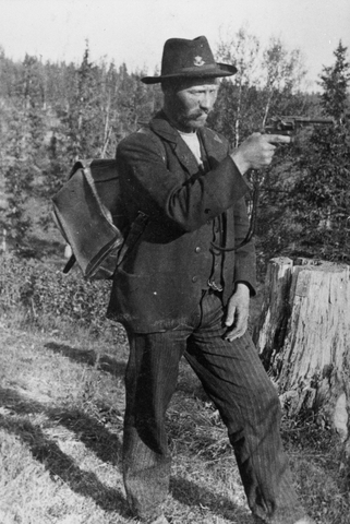 Lantbrevbärare Martin Jönsson iklädd privat hatt försedd med postemblem, siktar med revolvern. På ryggen har han en ränsel.