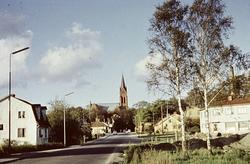 Bostadshus längs en gata i Mölndal. Fässbergs kyrka i bakgru