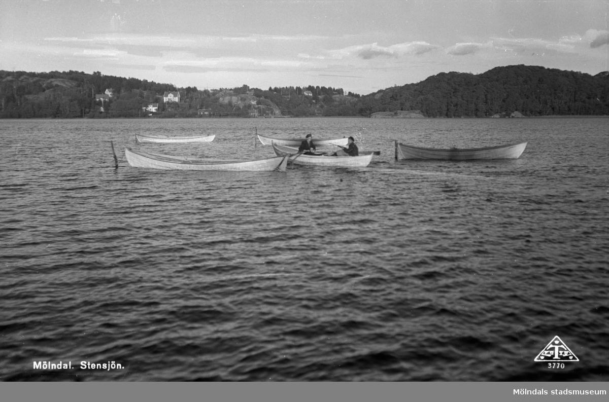 Två män i en eka. Vy över Stensjön från Strandpromenaden. På andra sidan sjön ses badplatsen vid Lilla berg.