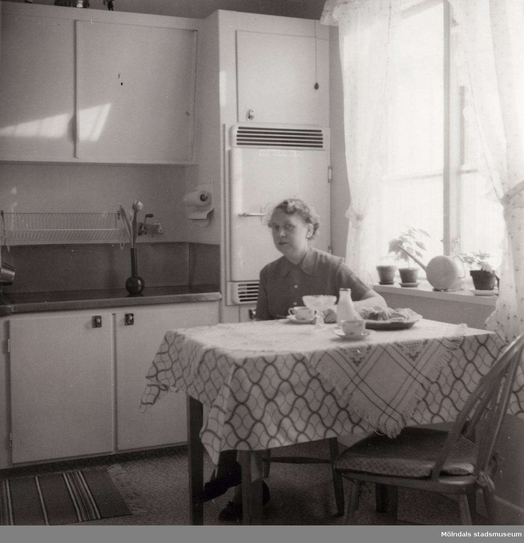 Inga-Lill Börjesson vid köksbordet på 1950-talet. Fotografi efter kylskåp installerats. Se även MMF2012:0048.