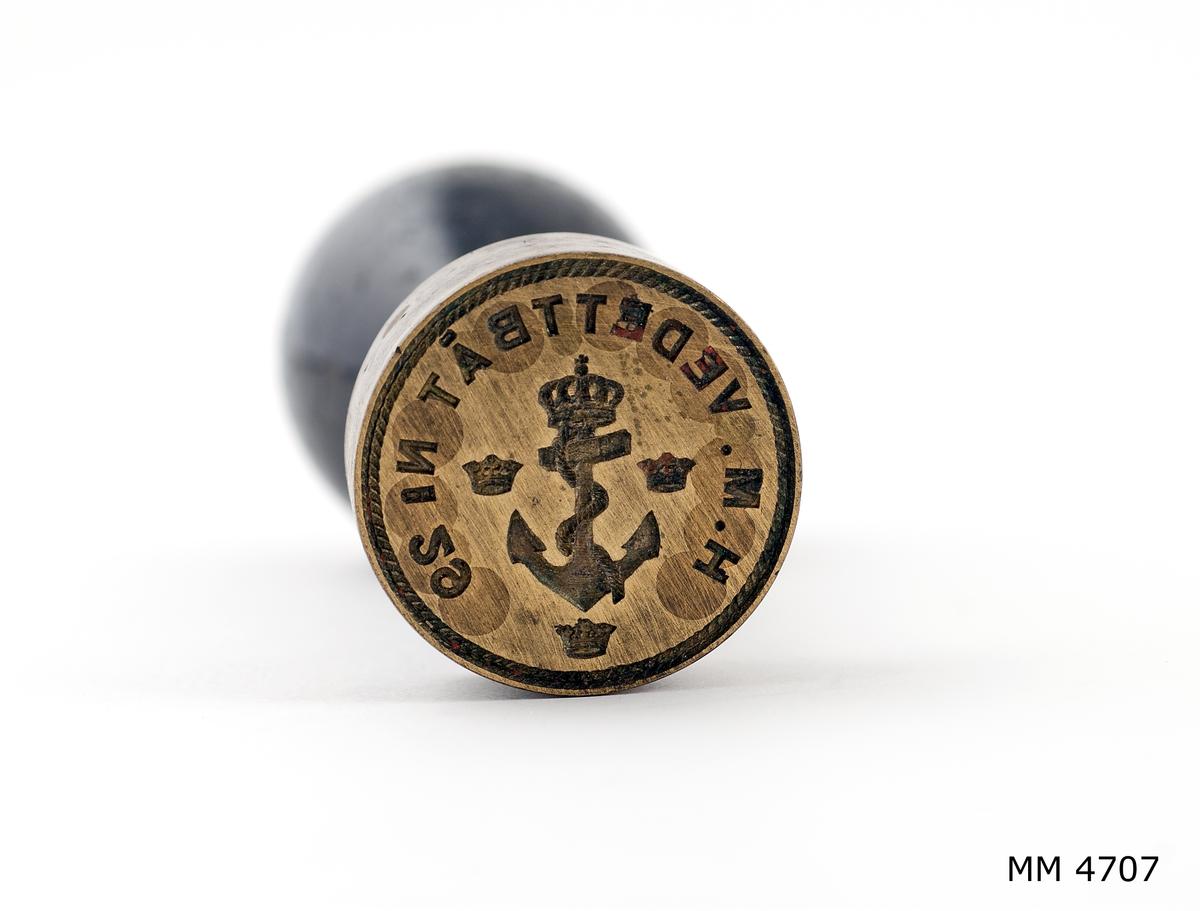 Sigill av mässing. Cylindriskt med svarvat handtag av svartpolerat trä. Text: H.M. Vedettbåt Nr 29, dessutom ankare med kunglig krona, omgiven av tre mindre kronor.