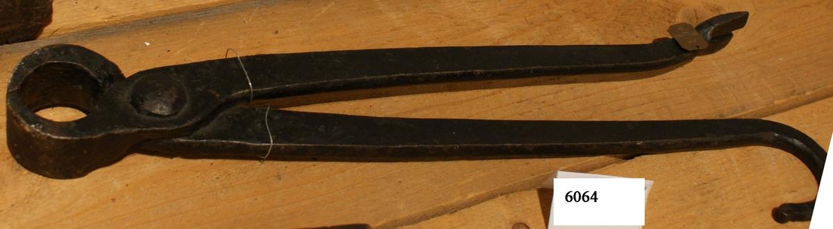 Avbitartång, större. Ena skänkeln försedd med upphugget spår för spikutdragning, den andra avrundad och bockad i krok för upphängning.