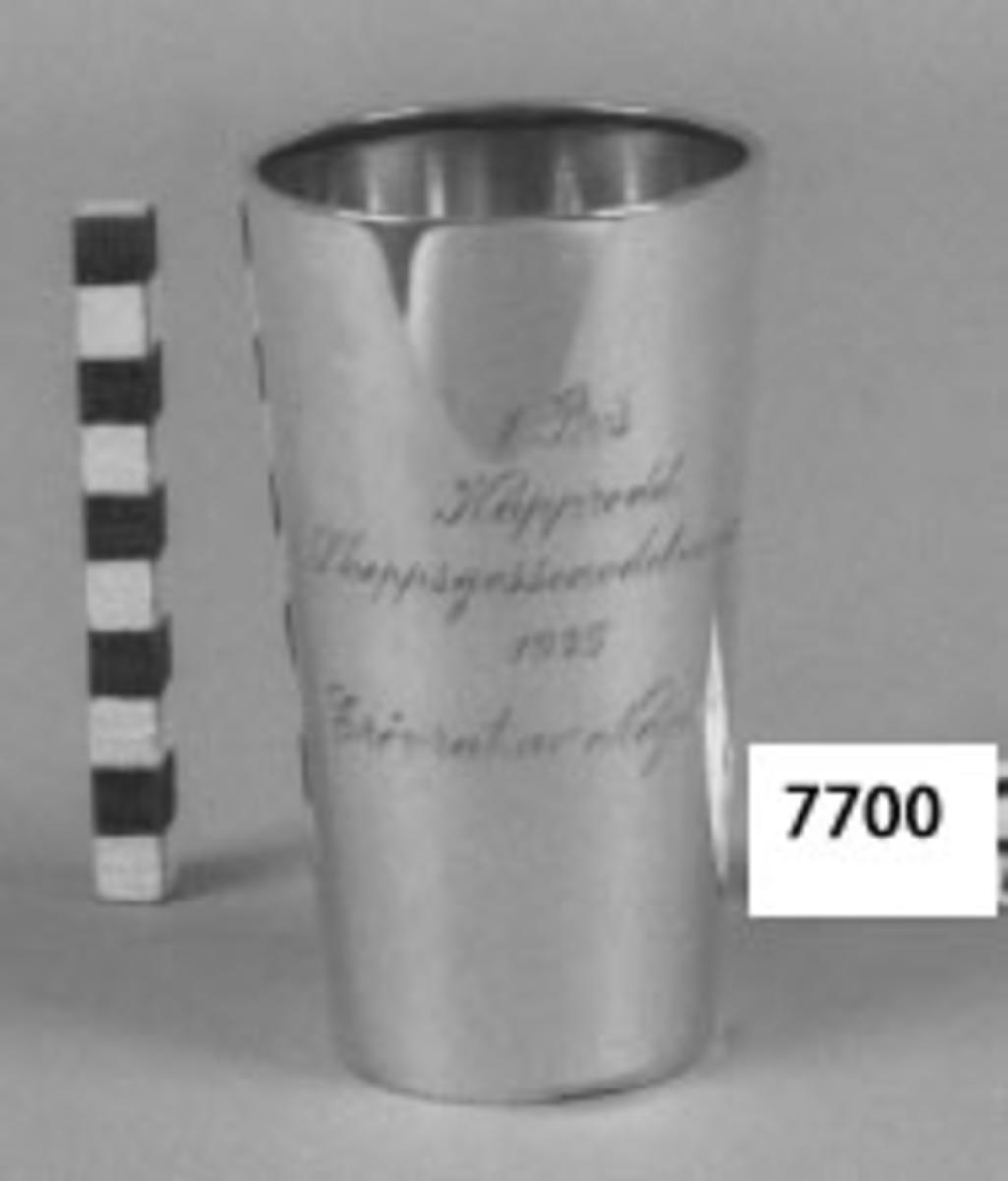 Bägare av silver. Utgör 1:a pris i kapprodd, erövrat av skeppsgossebriggen Najaden 1925. Inskription: 1 Pris Kapprodd Skeppsgosseavdelningen 1925 erövrat av Najaden.