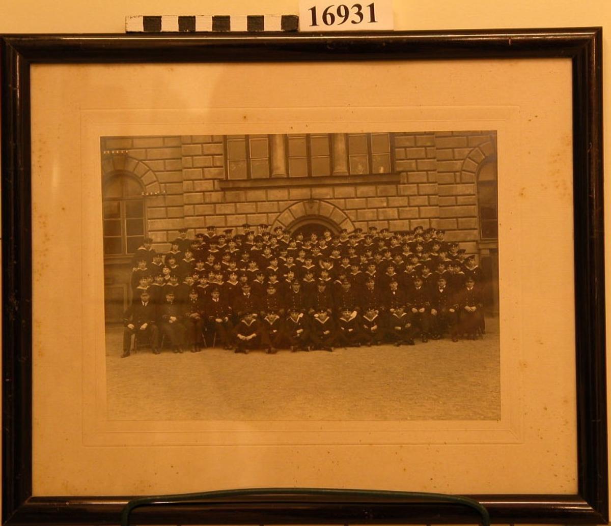 """Svartvitt fotografi inom glas och ram. Bilden visar skeppsgossar utanför  Skeppsgossekasernen (nuvarande Marinmuseum). 100-tal i olika åldersgrupper , bréfälen siter i främre raden. Fotografiet är placerad på """"falsk"""" passepartont, ramen av mahognybetsat trä, 18 mm bred. Baksida papp med glasmästarstämpel. Neg.nr A144  3:28A"""