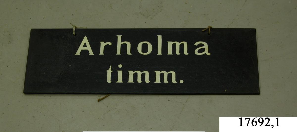 """Rektangulär skylt av masonite, framsidan svartmålad, hål för upphängning. Vit schablonmålad text: """" Arholma timm."""""""