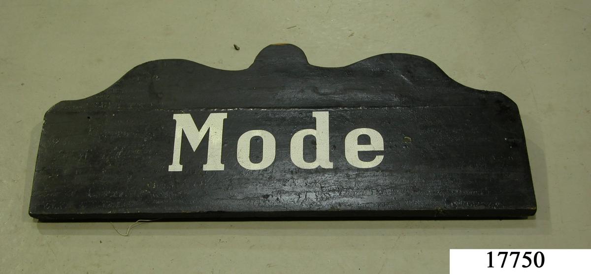 """Rektangulär skylt, ovansidan sågad i tre bågar, svartmålad. Vit schablonmålad text: """" Mode """"."""