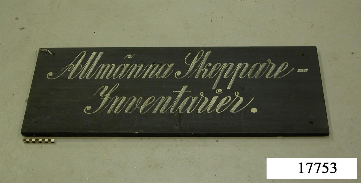 """Rektangulär skylt, svartmålad. Vit schablonmålad text: """" Allmänna Skeppare- Inventarier """", skriven för hand."""