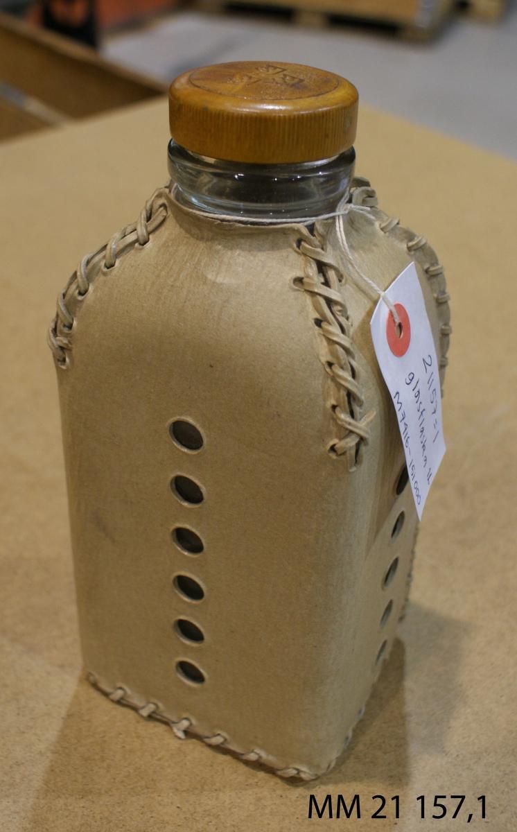 Flaska av glas, fyrkantig formklädd i läderskydd. Gul skruvkork märkt med tre kronor.