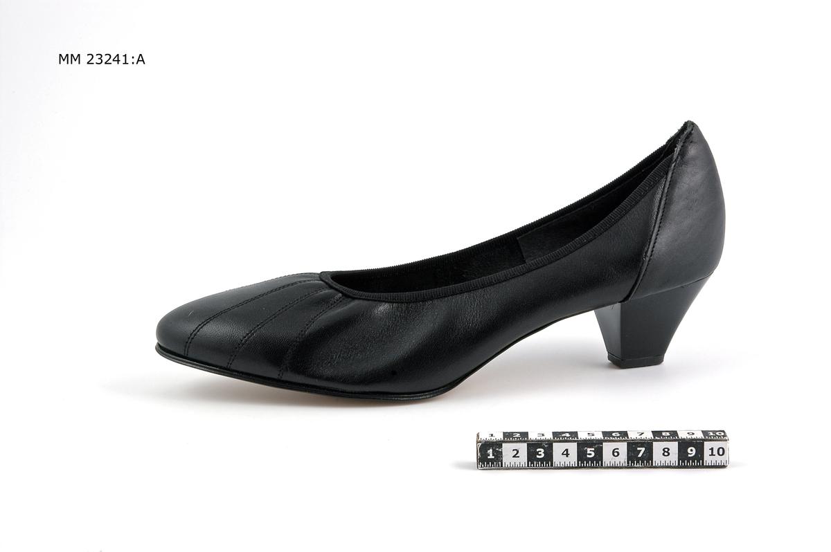 Svart damsko av typ pumps. Vänster sko.
