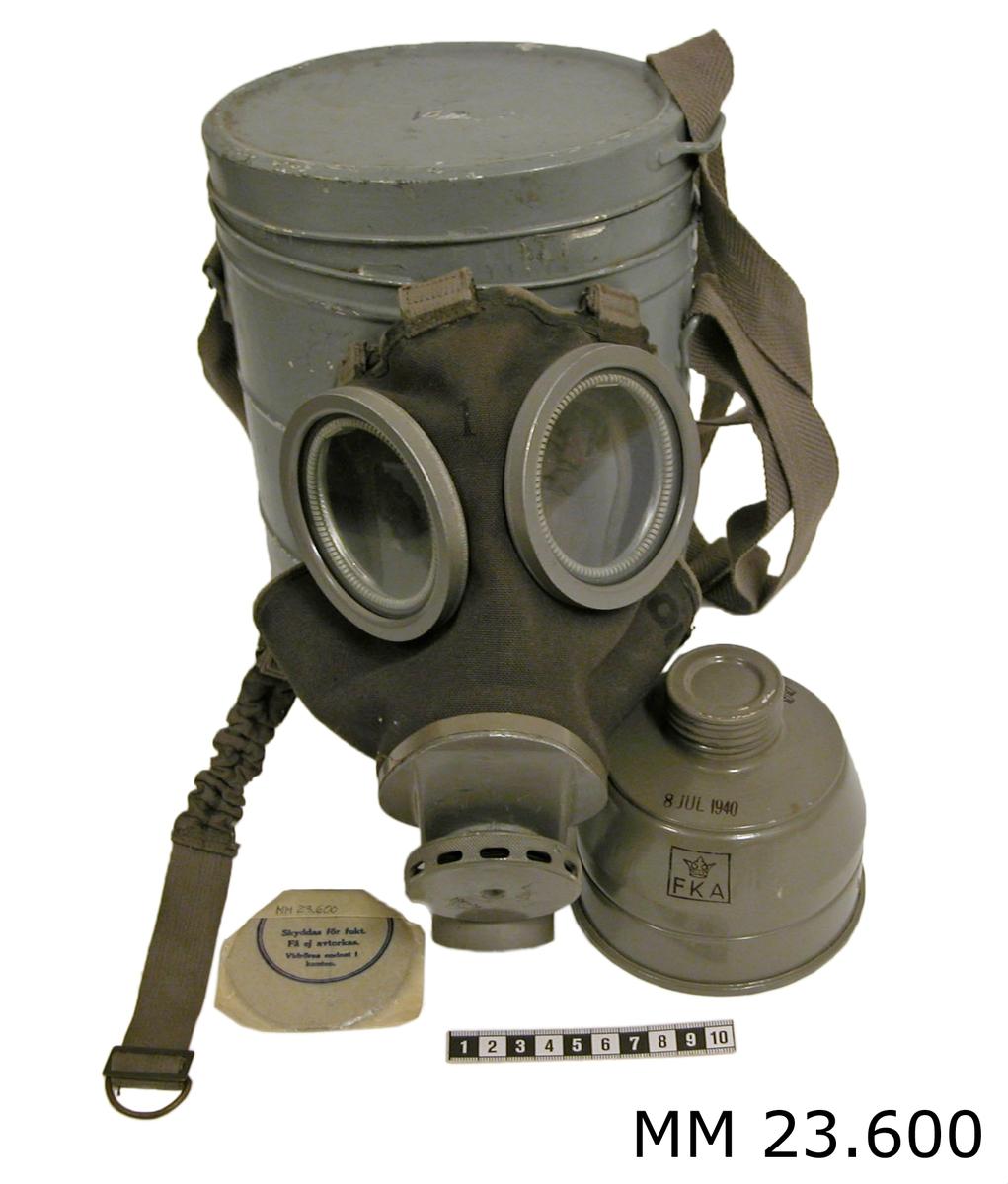 """Gasmasken består av: Ansiktsskydd med ventilhus och behållare. Ansiktsskyddet är av gastätt brungrått gummityg. Det är försett med infalsade ögonglas. Tätningsram av skinn för tätning mot ansiktet, bandställ med elastiska band för gasmaskens kvarhållande på huvudet samt munplatta av lättmetall med gängad anslutning för behållare och ventilhus. Masken är stämplad på utsidan: """" 1 samt 7103 """" på insidan flera stämplar """" 1 """" """" FKA krönt av krona inom en kvadrat """" tre kronor 24. FEB 1940 """". Behållaren är av metall med lock, oval form, gråmålad.På undersidan stämplad med tre kronor.Reglerbart bärband som locket är fäst i. I behålaren finns även ett paket med imskiva, stämplad F.K.Ä 24 JUL 1940 ULRIKSDAL. Ett gasfilter stämplat : """" tre kronor, 8 JUL 1940, FKA krönt av krona inom en kvadrat """" samt en torklappav grovvävd glestvinnad naturfärgad bomull. Se SSS och X pärm."""