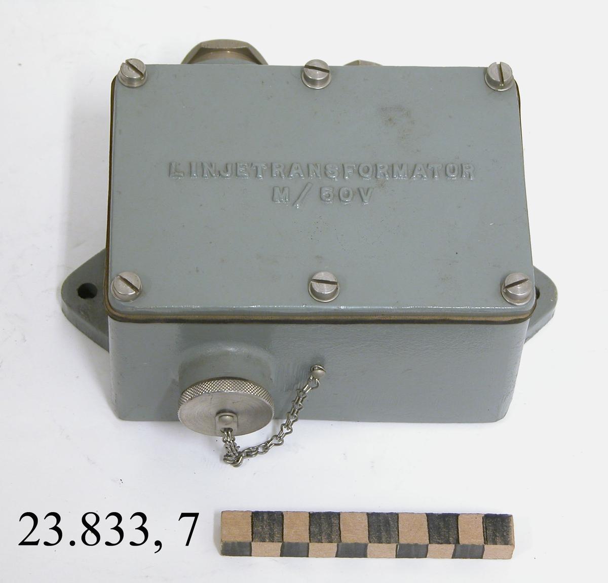 """Linjetransformator M/50C till Radiostation 50W FMUK-station m/44-51. Linjetransformatorn är rektangulär till sin utformning och målad i en gråtonad färg. På framsidan finns anslutningsmöjlighet för en anslutningskabel, denna är också försedd med ett påskruvningsbart metallskydd. På baksidan finns anslutningsmöjlighet för två olika anslutningskablar. Linjetransformatorn kan fästas i vägg eller tak via två utskjutande skruvhålsplattor som finns nedtill på apparaten. På ovansidan är apparaten märkt i relieftext med: """"LINJETRANSFORMATOR M/50V""""."""