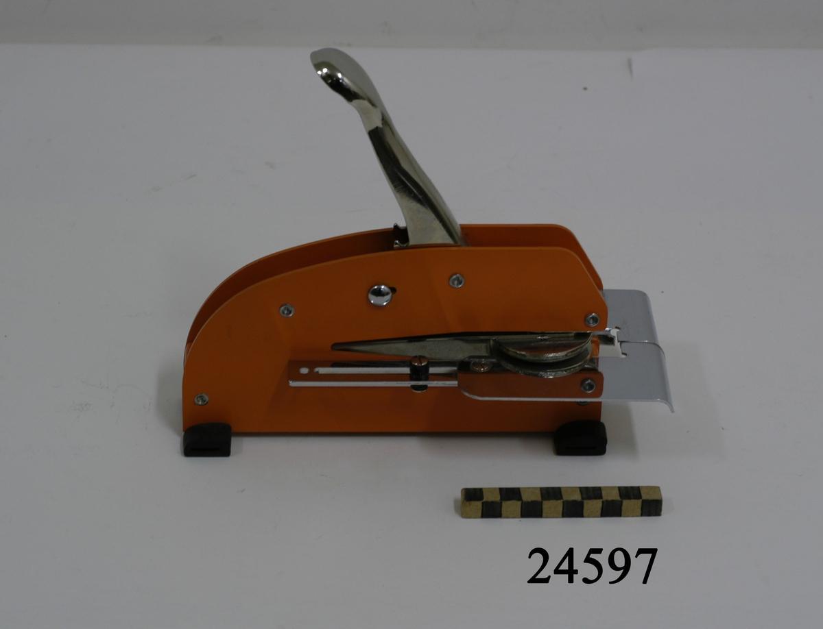"""Präglingsmaskin av metall, orange, stående på fyra svarta gummifötter. Försedd med metallfärgat handtag och stans. I höjd med, och på vardera sida om stansen metallfärgade justerbara bleck. Stanspräglingen: En cirkel, i mitten ett stockankare, längs cirkelns innerkant text. """" CHEFEN FÖR BERGA ÖRLOGSSKOLOR """". På handtaget ingraverad text: """" REGULATION """" samt """" Justrite """". På ett av metallblecken ett fasttejpat präglingsprov."""