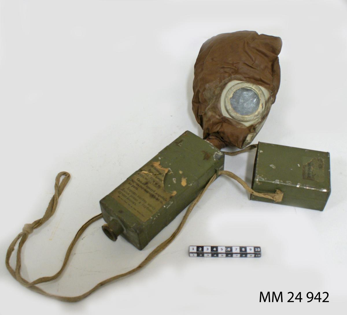 """Gasmask, Zelinsky Kummant modell 16 kallad """"Moscow"""". Rektangulär låda av plåt, grönmålad. Avtagbart lock som rymmer masken. Masken är av brunt gummi med runda titthål av glas. Gasmasken är fäst i pipa i filterlådan. Filtret är ett kolfilter med en linning av bomull som hindrar inandning av kolet. Pipa i filterlådans botten. Locket och filterlådan sitter sammen med textilsnöre som även gör att gasmasken kan hängas runt halsen. Diverse pappersettiketter med rysk text sitter på filterbehållaren: """"CEPIR 296"""" mm."""