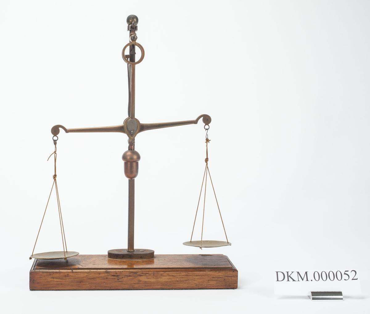 Skålvekt som er montert på en treplate. Vekta har ingen skala, men to visere som skal passe mot hverandre når vekta er i likevektsposisjon. De to skålene er runde.