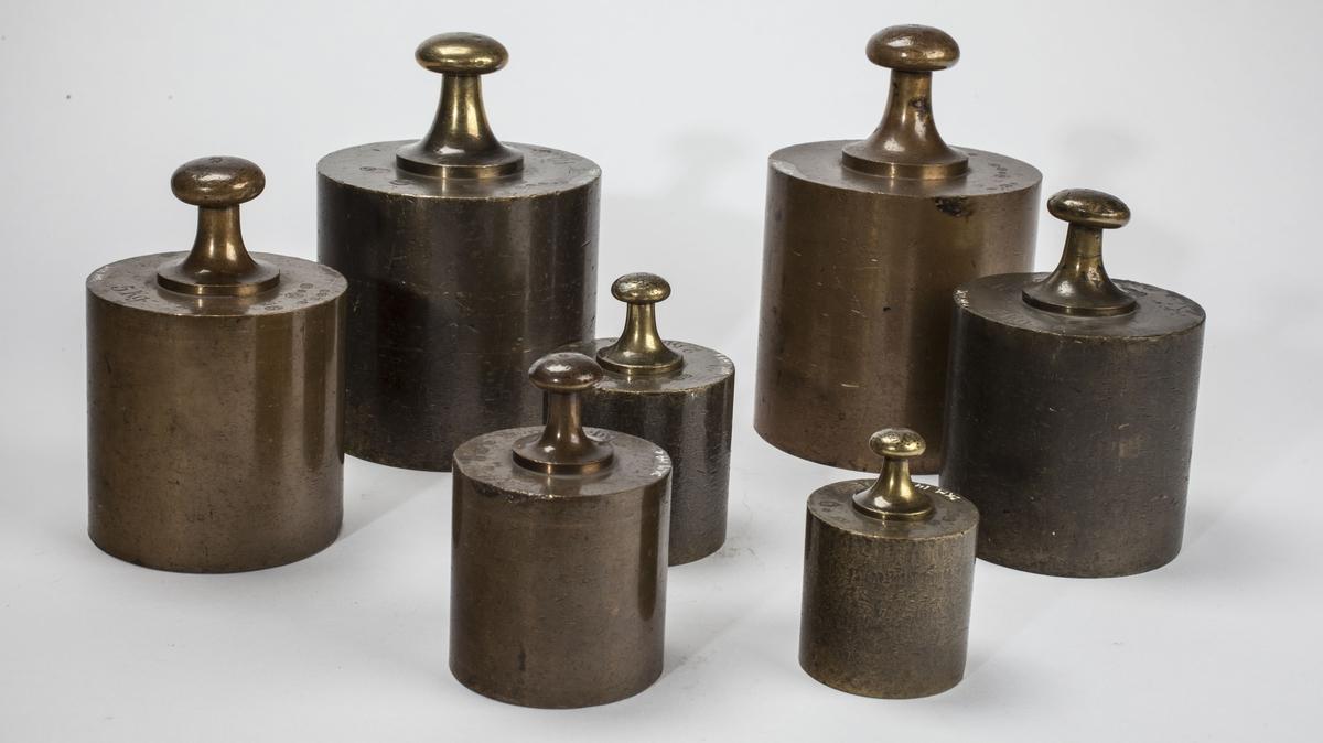 Sju sylinderformede lodd i ulik størrelse. Kontrollstempel i hvert lodd.