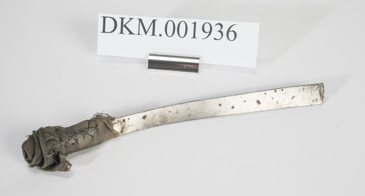Ett avlangt, avkappet metallstykke hvor det er snurret en bit tøy rundt den ene enden.