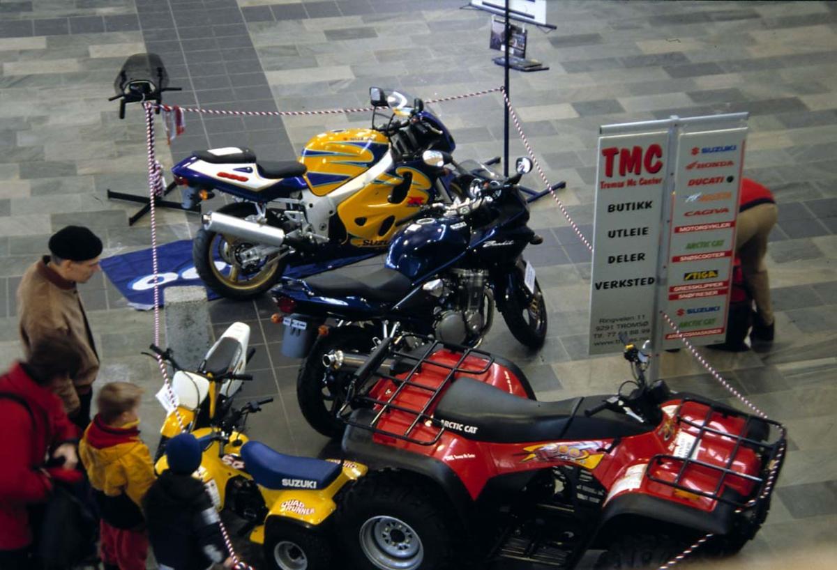 Lufthavn. Utstilling av motorsykler i terminalen. Flere personer.