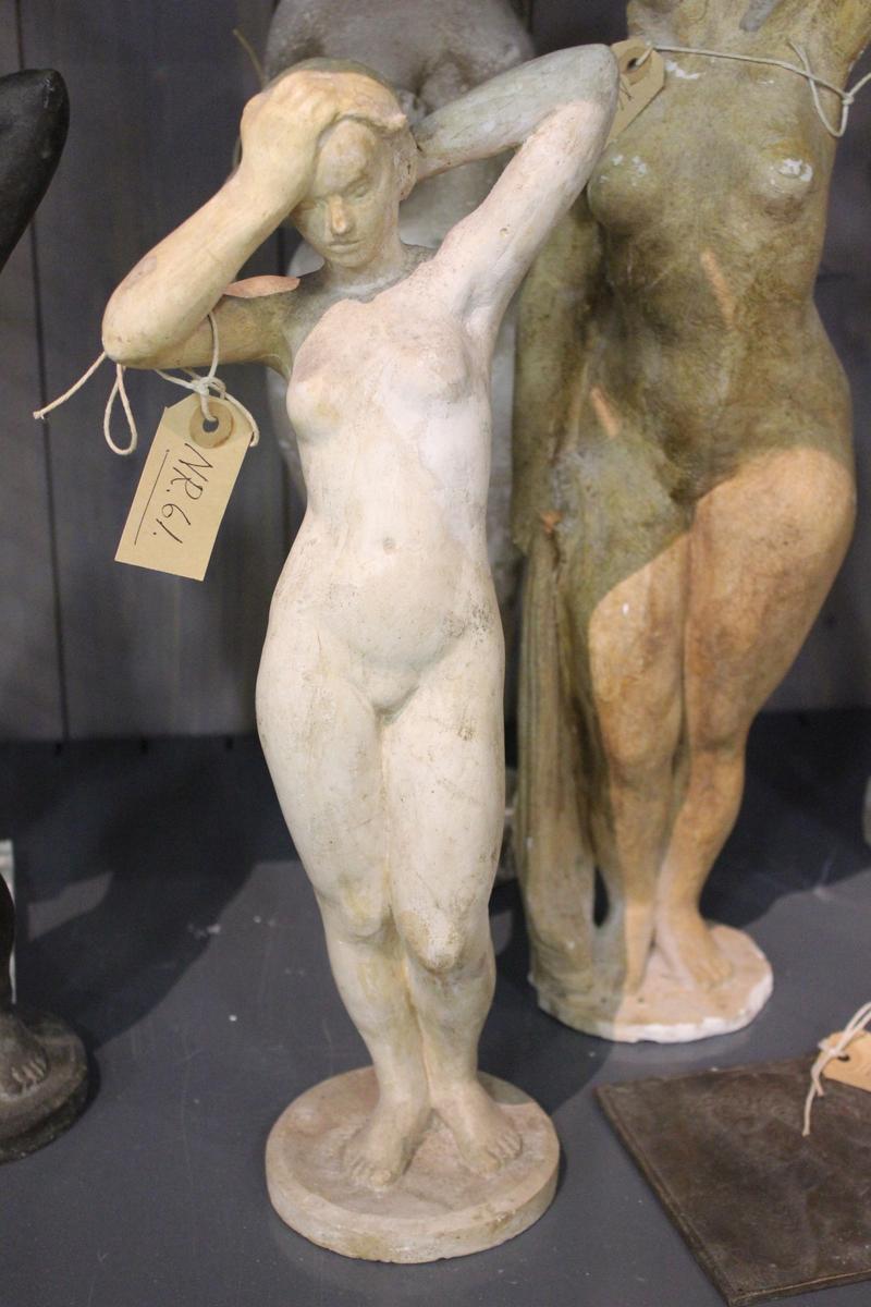 Skulptur i gips av en pike som steller håret sitt.