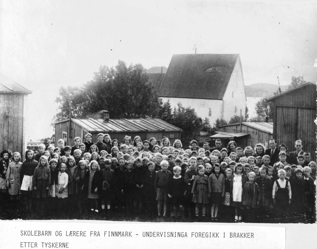 """Elever og lærere ved grunnskolen i """"Finnmarksleiren"""". Trondeneskirka i bakgrunnen."""