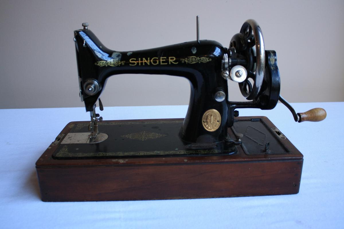 Symaskin med handsveiv på tresokkel. Verktøyskrin intregrert i tresokkelen. Heile maskina er dekorert  med blomster og div. mønster i gult.