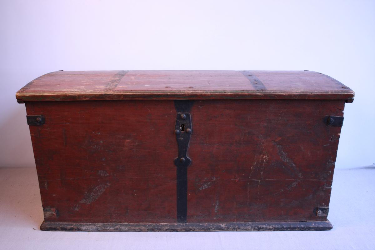 Kiste med svakt bua lok. Handtak i metall på begge sider. Metallbeslag over lås og hjørner. Metallnagler i lok. Lås og nøkkel er øydelagt, ikkje mogleg å få opp kista. Sett saman med sinking. Raudmålt med svart dekor. Spor etter grøn måling på loket.