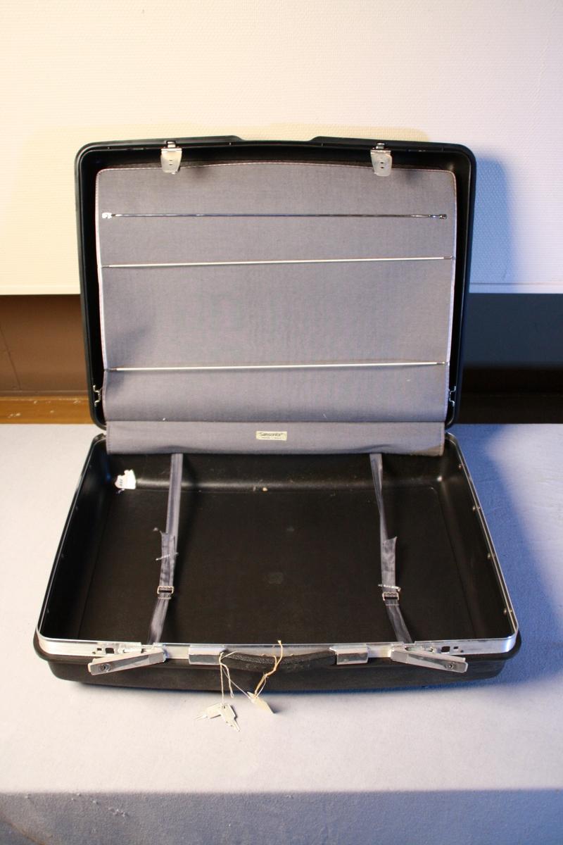 Fin koffert, i fard plast. Handtak og to låsar. Innsida er har to rom der det er mogleg å henge opp klær med kleshengarar i det eine rommet. 3 kleshengarar følgjer med.