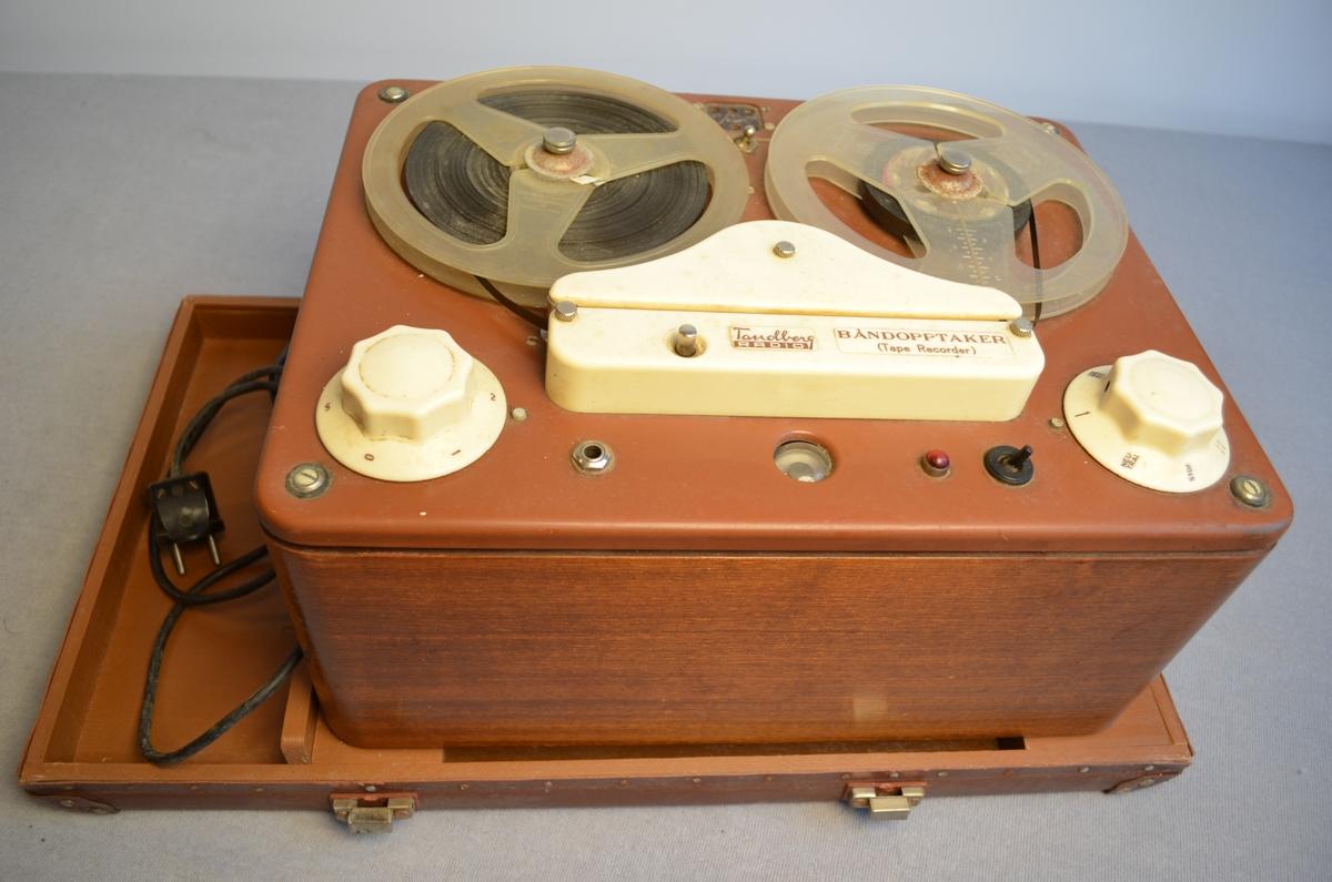 Tandberg banopptakar med tilhøyrande koffert i vulkanfiber. Kofferten er av merket Unica. I loket på kassa er det ein høgtalar. Stempel- og omsetningsavgift under bandopptakaren og inni loket. Dato 9.4.1951.