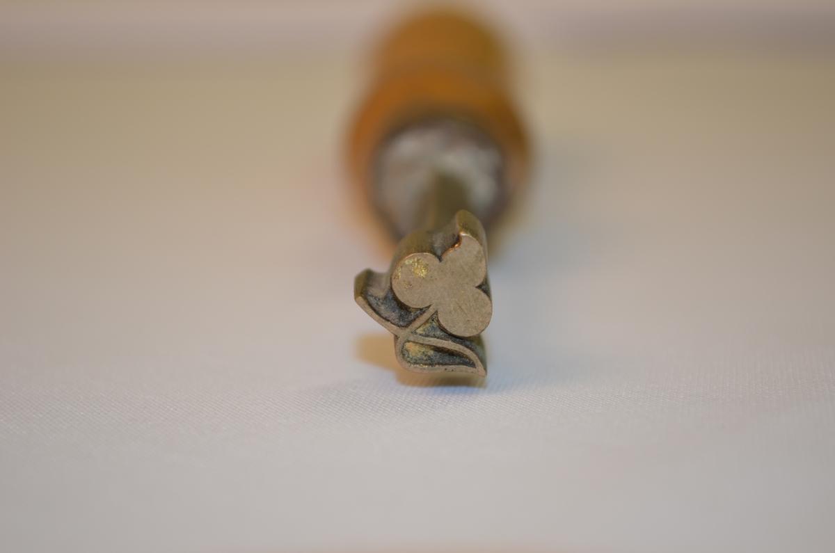 Stempel i jarn med treskaft. Motivet er ein trekløver. Mest truleg nytta til dekorering av skinnpermar til bøker. Denne låg i ei verktøykasse frå ein boktrykkar.